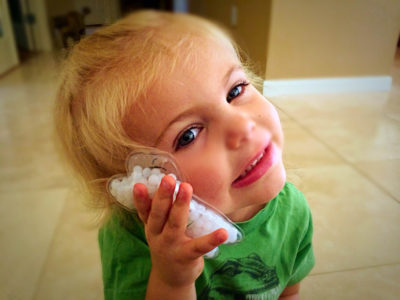 Adorable blonde toddler holding tooth-shaped gel pack to her cheek.